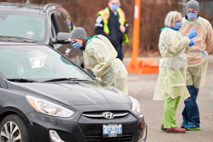 Health care workers speak with patients at a drive-thru Covid-19 assessment centre in London, Ont., on March 17, 2020.