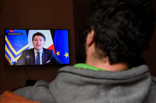 TURIN, ITALY - 2020/03/16: A man watches Italian Prime Minister Giuseppe Conte on TV announcing new economic...