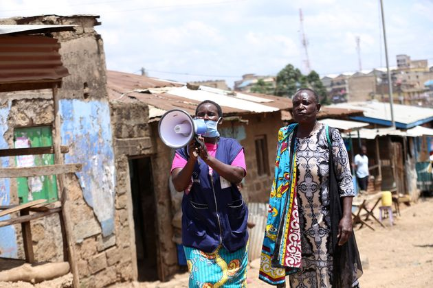 A health volunteer walks through slums in Nairoba, Kenya, informing residents about the coronavirus pandemic....