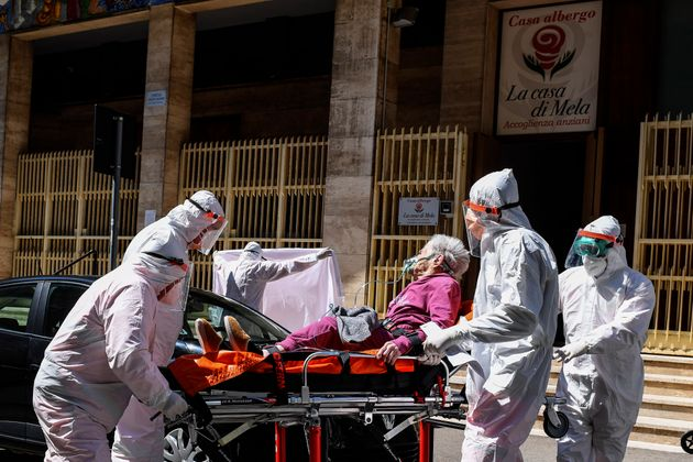 NAPLES, CAMPANIA, ITALY - 2020/04/02: Health workers wearing protective suits, gloves and masks transfer...