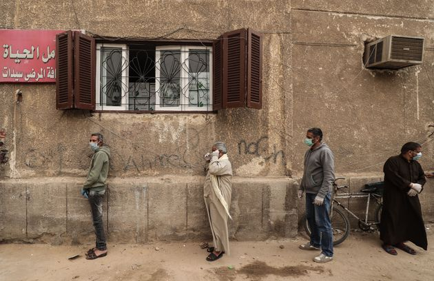 Men wearing masks wait outside an Egyptian Food Bank center in Cairo to receive cartons with foodstuffs...