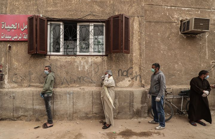 Men wearing masks wait outside an Egyptian Food Bank center in Cairo to receive cartons with foodstuffs as the charity distri