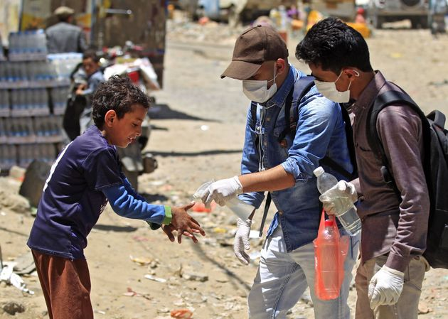 A volunteer in Sanaa, Yemen, sprays disinfectant on the hands of a boy in the one of the city's poor...