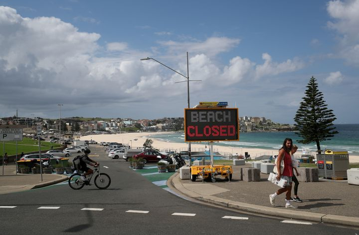 "People walk past a ""Beach Closed"" sign at Bondi Beach, as the beach remains closed to prevent the spread of the coronavirus disease (COVID-19), in Sydney, Australia April 1, 2020. REUTERS/Loren Elliott"