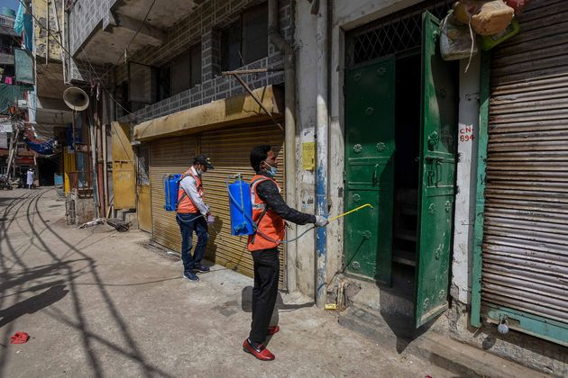 A municipal health worker sprays disinfectant while sanitising shops and homes at Gandhi Park at Hauz...