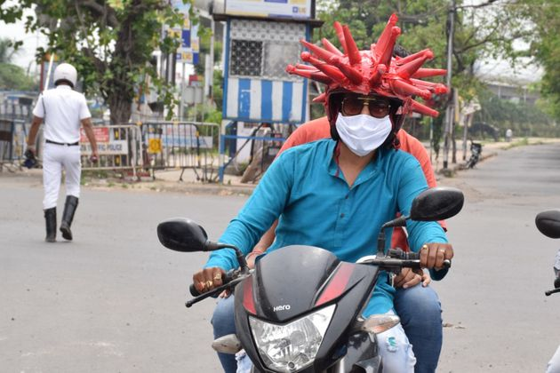 Volunteers wearing a coronavirus-themed outfit composed of helmet to raise awareness about the coronavirus...