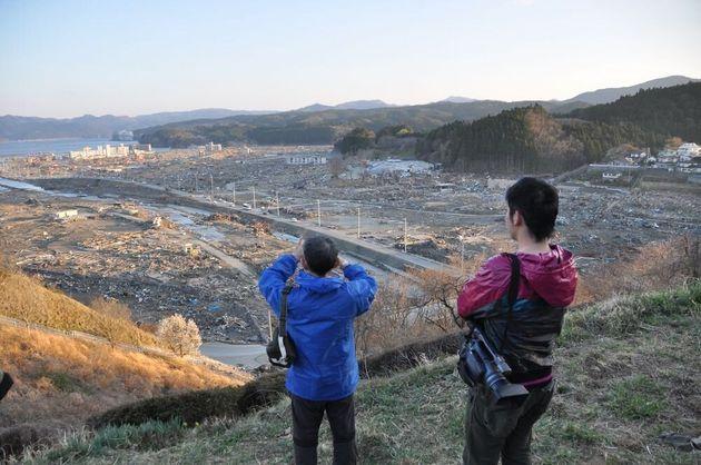 高台から流された街を見る牧さんと川口さん=2011年4月16日、宮城県南三陸町