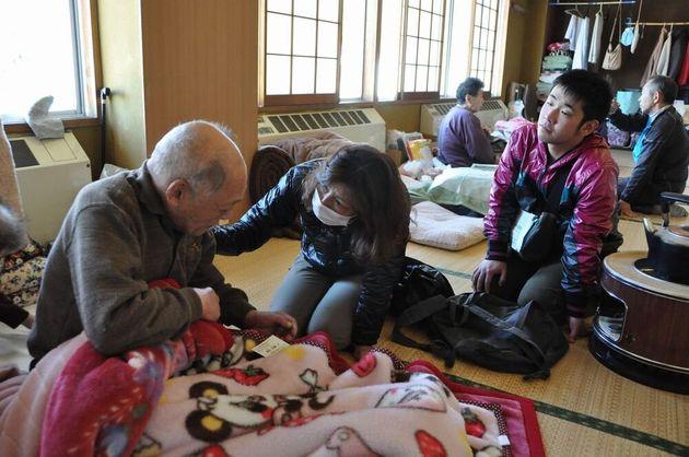梶田さんは老夫婦の話に涙を浮かべ、時折背中をさすり話を聞いていた=宮城県石巻市の避難所