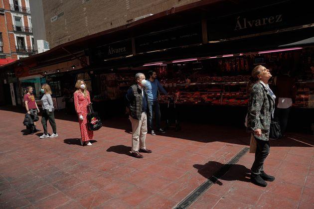 Una cola de gente en Madrid, manteniendo la distancia física mientras aguardan para