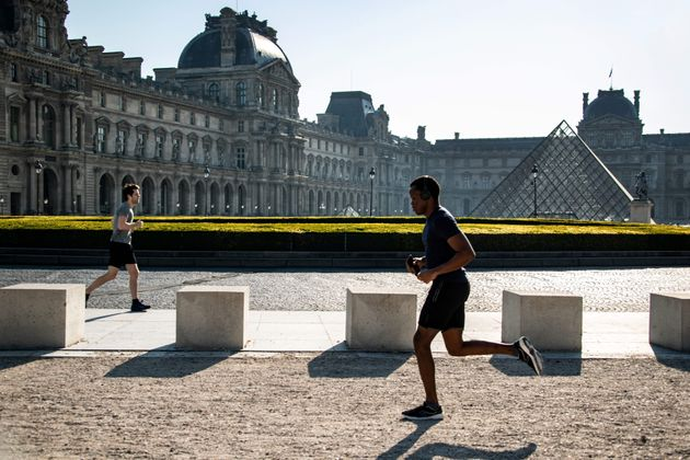 A jogger runs near the Louvre pyramid, early on April 09, 2020, as new restrictions forbidding sports...
