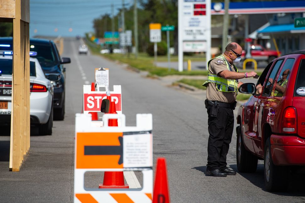 An officer with the Dare County Sheriff's Office inspects the identification of a driver entering the Outer Banks. This coron