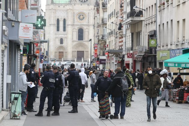 Des policiers français contrôlent l'attestation de sortie d'un homme à Saint-Denis,...