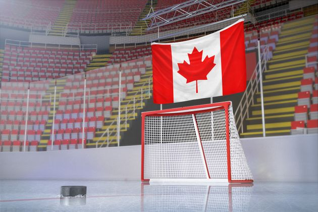 In this stock photo, an empty hockey arena is seen with a Canadian flag hanging in the bleachers. It...
