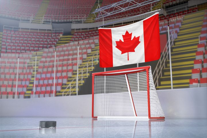 In this stock photo, an empty hockey arena is seen with a Canadian flag hanging in the bleachers. It may be a long time before anyone sees an NHL game in person, a new report on the impact of COVID-19 on Canada says.