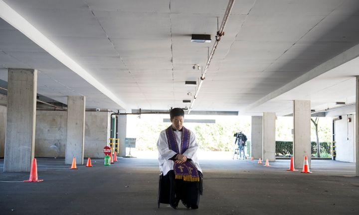 Assistant Pastor at St. Patrick's Parish Father Felix Min waits for a car to pull up during a drive-thru confession in a parking garage at the church in Vancouver on April 8, 2020.