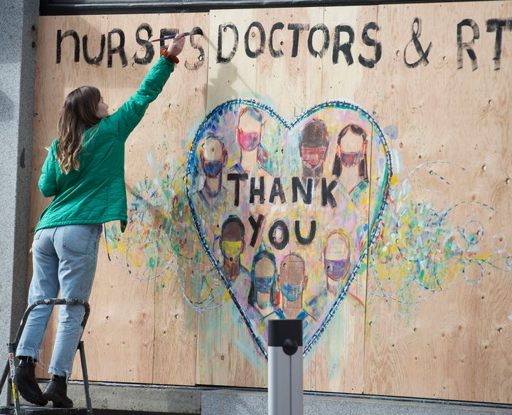 A woman paints a thank you message to nurses and doctors on a boarded up shop in downtown Vancouver on April 1, 2020.