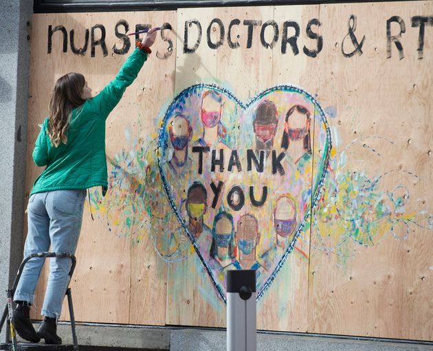 A woman paints a thank you message to nurses and doctors on a boarded up shop in downtown Vancouver on...