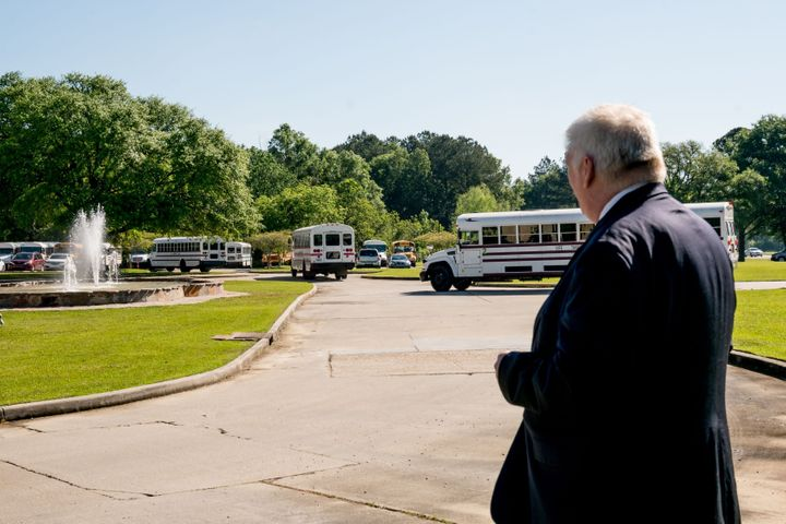 Joe Long, an attorney working with Pastor Tony Spell, watches as buses bring congregation members to Life Tabernacle Church f