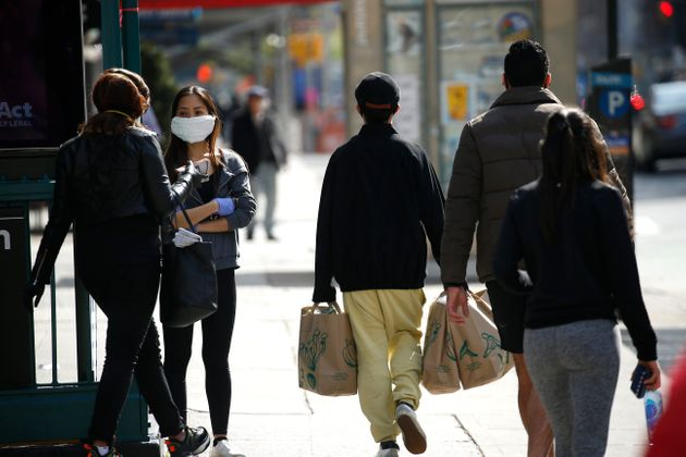 NEW YORK, NY - APRIL 07: A woman wearing a mask looks on as passerby walk on 7th avenue amid the coronavirus...