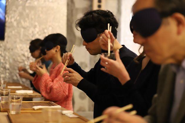 アイマスクを着けてごはんを食べる参加者たち