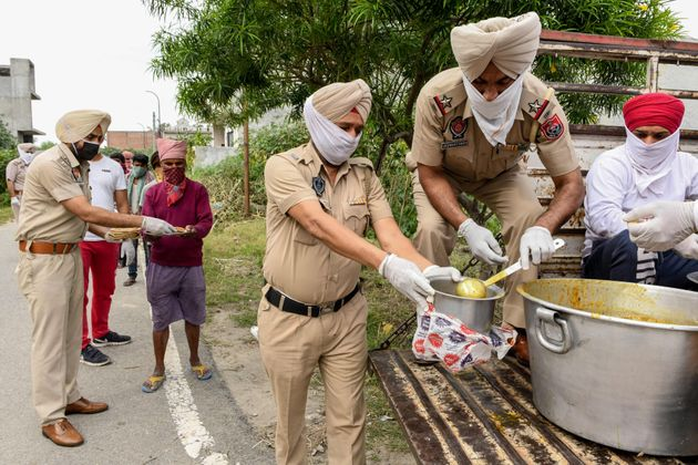 Police personnel distribute food to people during the lockdown, on the outskirts of Amritsar on April...