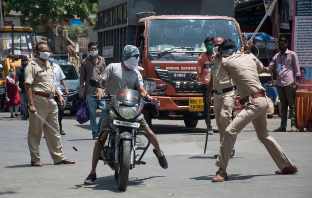 Police officials punish people who came out during the lockdown at Bhandup, Mumbai on April 4,