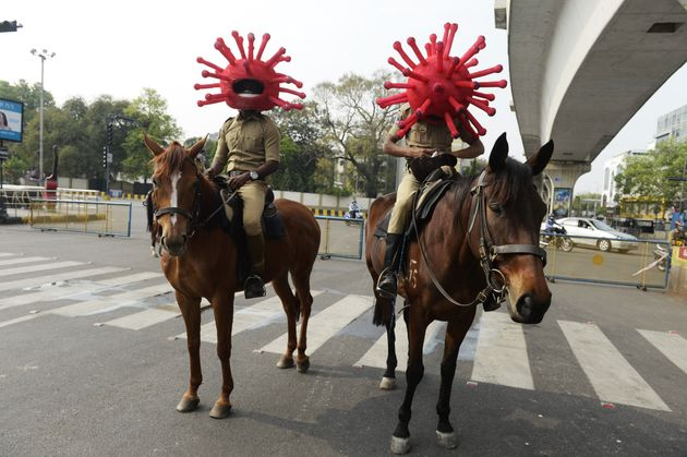 Police personnel wearing coronavirus-themed helmets ride on horses as they participate in an awareness...