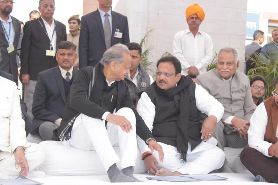 Rajasthan Health Minister Dr. Raghu Sharma (second from right; black shawl around neck) speaks with Chief...