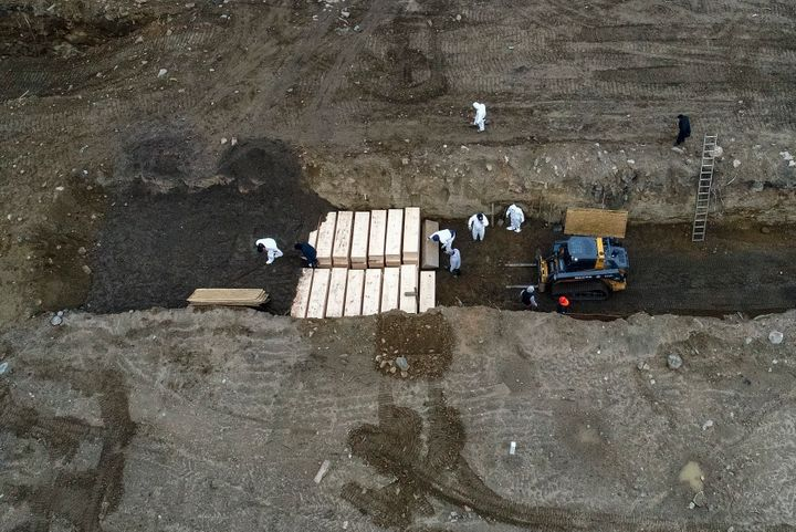 Workers wearing personal protective equipment bury bodies in a trench on Hart Island, which is in the Bronx borough of New York City, earlier this month.