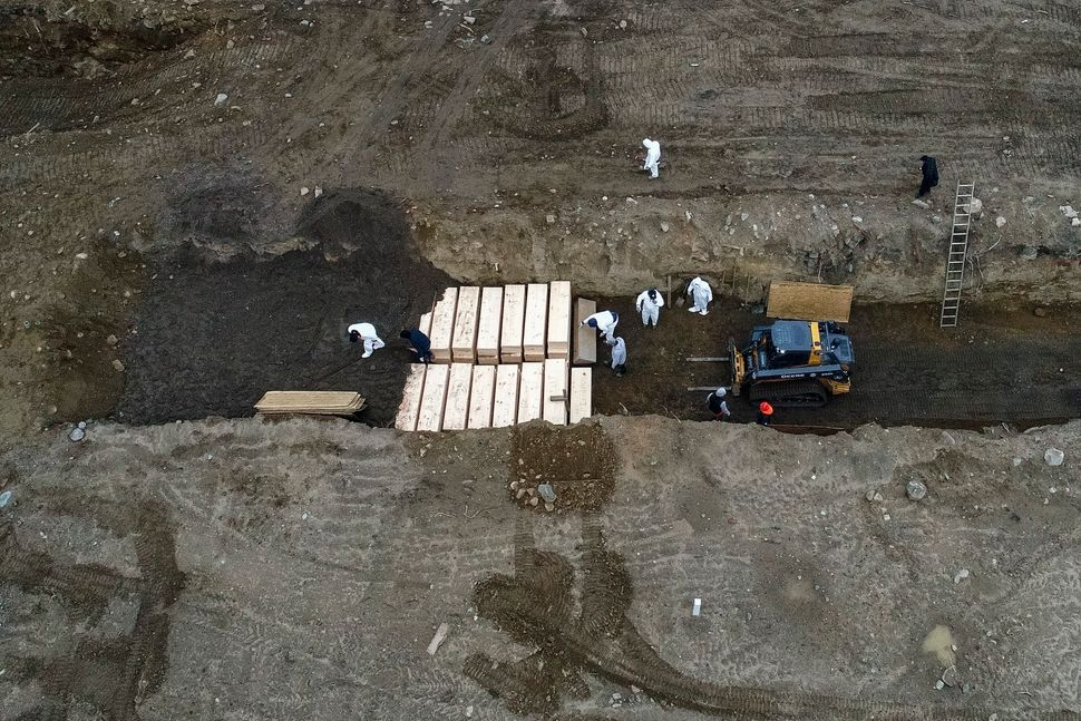 Workers wearing personal protective equipment bury bodies in a trench on Hart Island, which is in the Bronx borough of New Yo