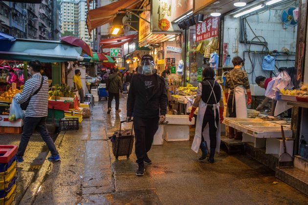 홍콩의 한 시장에서 마스크를 끼고 얼굴을 가린 채 걸어가는 시민. 2020. 4.