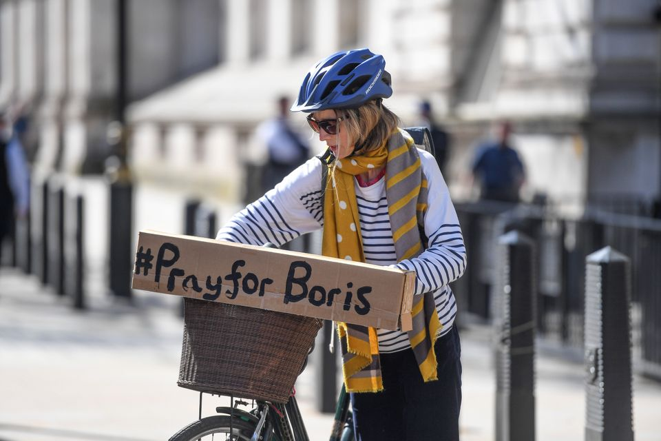 A cyclist with a sign reading '#PrayforBoris' rides through Westminster.