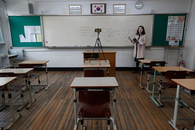Teacher Chung Ha-eun gives an online class amid the new coronavirus outbreak at Seoul girls' high school in Seoul, Thursday, April 9, 2020. Senior high school students begin school semester with online classes.  Schools remain closed as part of measures taken by the government to stop the spread of the coronavirus. (AP Photo/Ahn Young-joon)