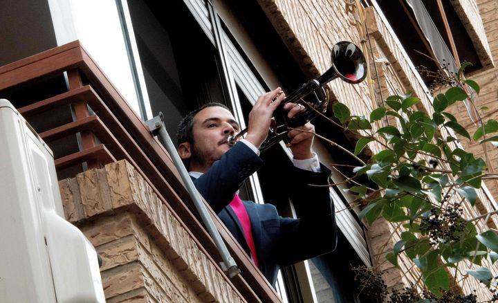 Un hombre toca la trompeta desde su balcón.