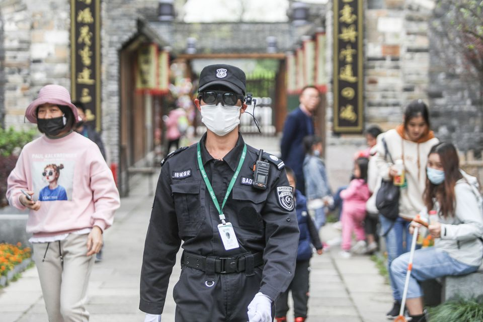 A security guard wearing augmented reality eyewear equipped with an infrared temperature detector walks...