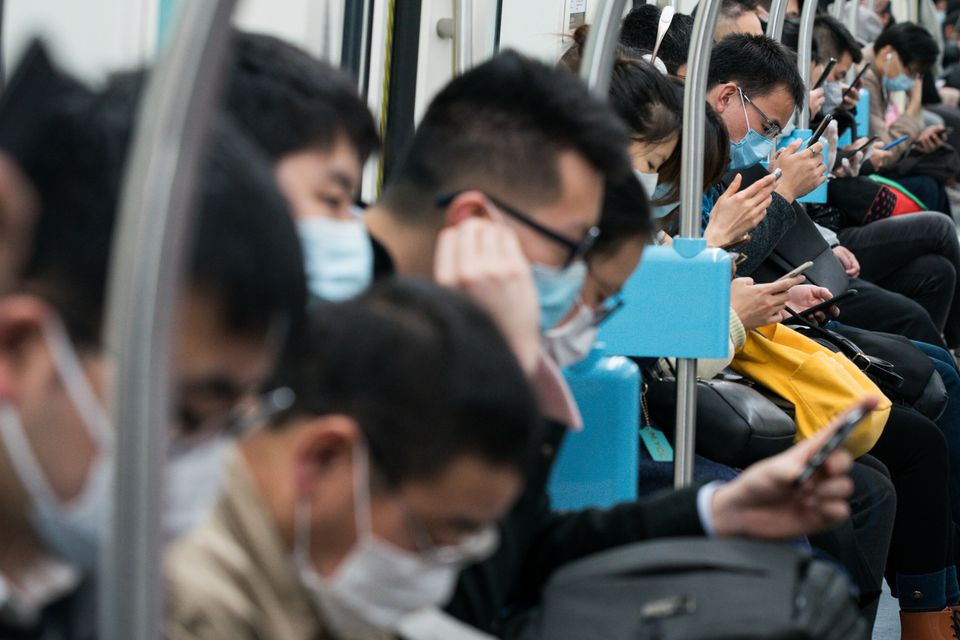 Commuters in protective masks look at their smartphones while riding a subway train in