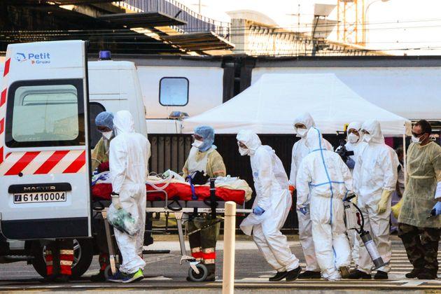 Des soignants prennent en charge un malade du coronavirus après son arrivée par TGV médicalisé...