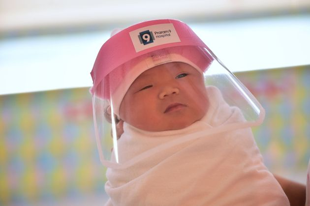 A newborn baby wearing a face shield at a hospital in