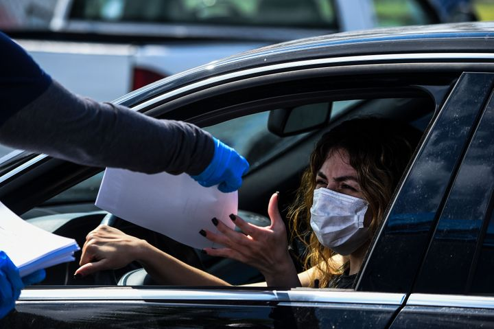 A woman collects unemployment forms at a drive-through collection point outside John F. Kennedy Library in Hialeah on April 8.