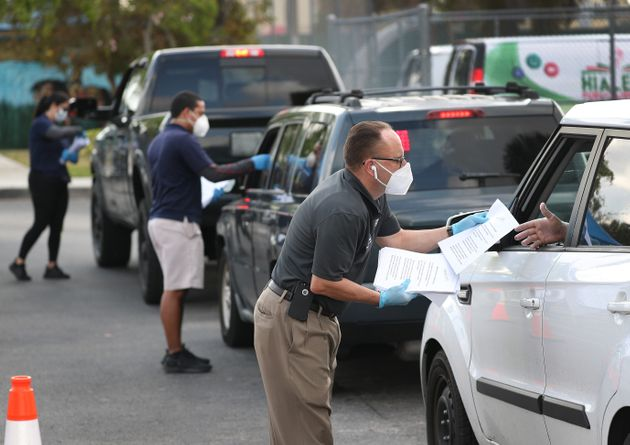 Eddie Rodriguez (right) and other Hialeah city employees hand out unemployment applications to people...