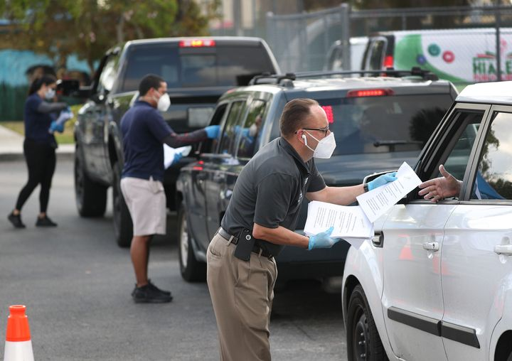 Eddie Rodriguez (right) and other Hialeah city employees hand out unemployment applications to people in their vehicles in front of the John F. Kennedy Library on April 8.