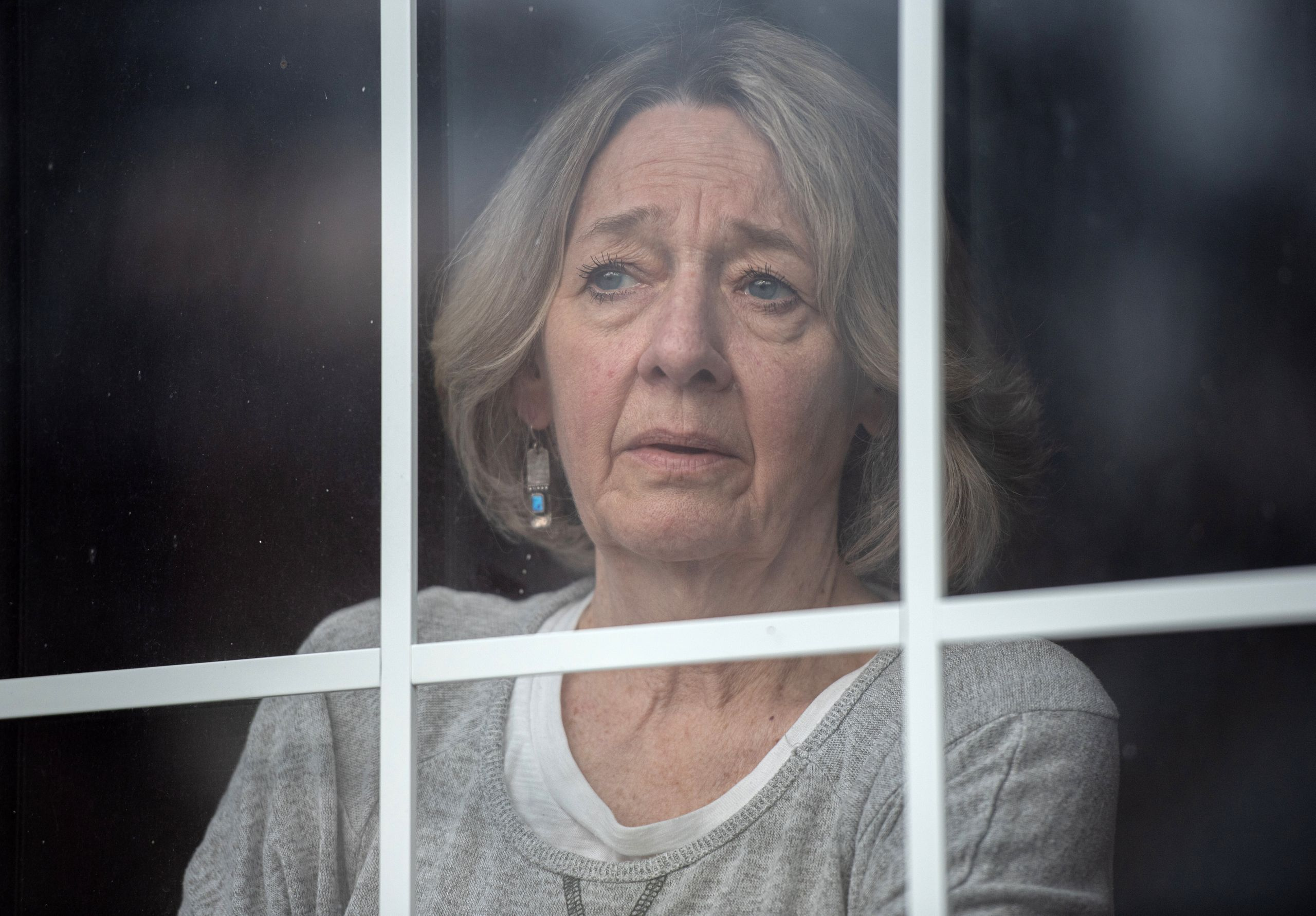 Linda Beaupre gazes out a window of her home on Wednesday. She lost her husband of 35 years to COVID-19.