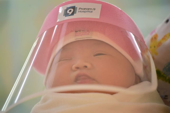A snoozing infant wearing the face shield.