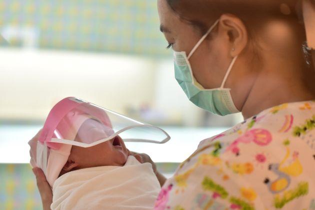 ラーマ9世病院で、フェイスシールドをつけた新生児を抱く看護師