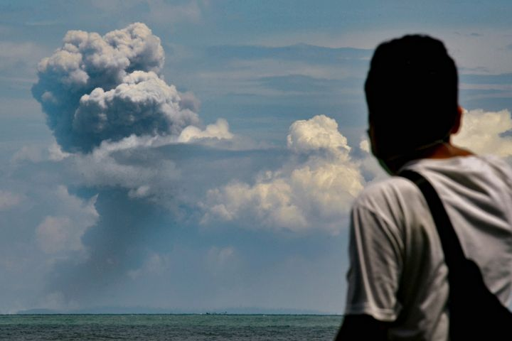 A man watches Krakatau spewing ash during an eruption, in Serang, Indonesia's Banten province on April 11, 2020. (Photo by RO