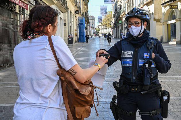 Une agente de la police municipale vérifiant l'attestation d'une passante, à Montpellier,...