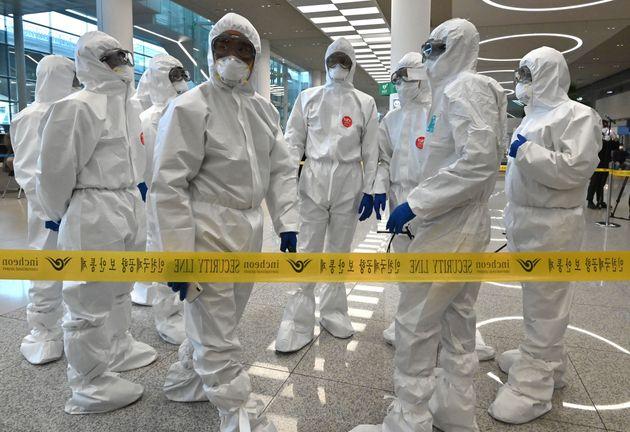 보호복을 착용한 경찰관들이 인천국제공항에서 귀국하는 승객들을 안내하고 있다. 2020년