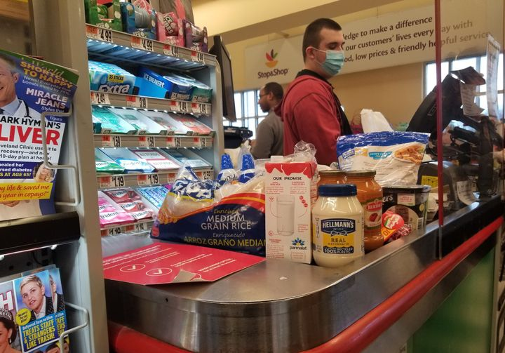 A masked cashier rings up purchases behind a plexiglass shield at a Stop and Shop grocery store in Queens, New York.