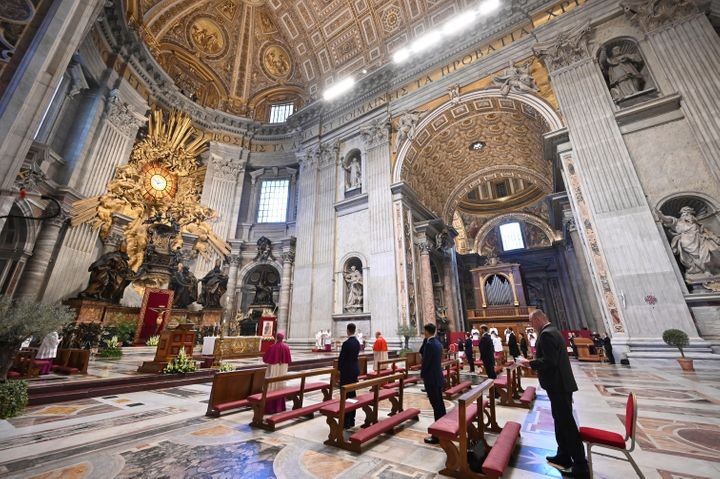 Few faithful attends Pope Francis', small white figure at center, Easter Sunday Mass, inside an empty St. Peter's Basilica at