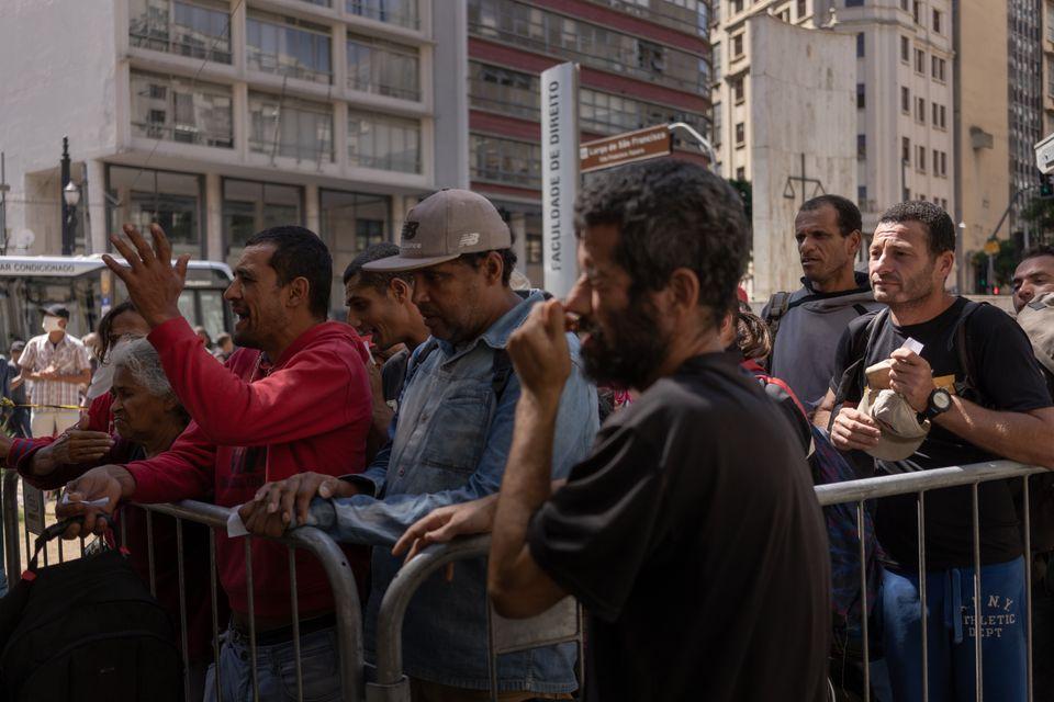 Des sans-abri font la queue pour obtenir des vivres devant un centre de dépistage, à São